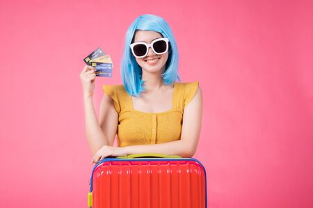 Portrait of a pretty excited asian girl with colorful baggage on  isolated over pink background Asian travel  woman carrying in colorful for summer trip concept young blue hair girl Foto de archivo - 135627887
