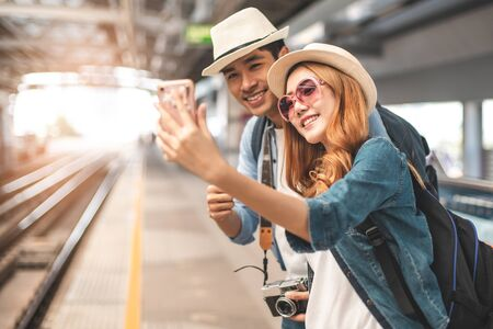 Happy Asian couple traveler holding a mobile phone in station and waiting for train in vacation time.Two Asian Tourists With Backpacks Train travel in Sightseeing City Thailand. Foto de archivo - 138331283