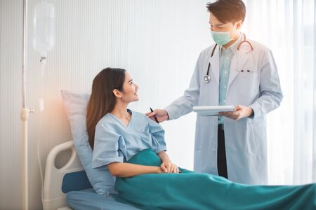 Medicine and health care concept. Asian doctor is taking care patient woman in hospital.doctor or nurse wear protection mask checking and take care infection people from covid-19 .