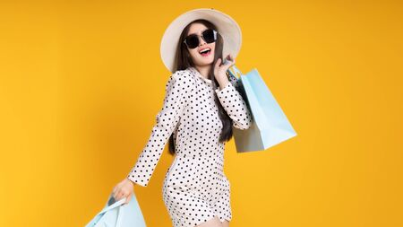 Asian pretty young woman on yellow colour background. She smiling and happy shopping bags. she nice-looking lovely attractive shine .Summer Sale colourful happy time.