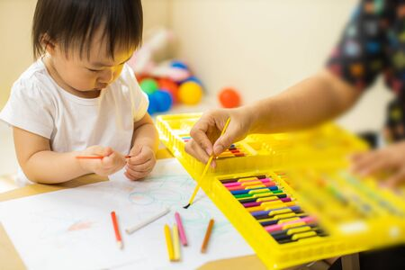 Cute asian little girl is painting the color with fully happiness moment , concept of art and education for kid.toddler girl practice paiting for homeschooling.Lovely asian girl drawing with colored pencil