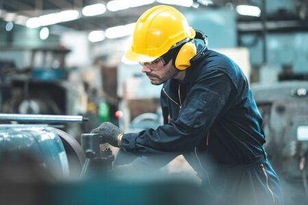 Industrial Engineers in Hard Hats.Work at the Heavy Industry Manufacturing Factory.industrial worker indoors in factory. man working in an industrial factory.Safety first concept.