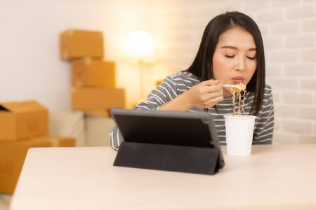 Asia freelance  business woman eating instant noodles while working on laptop in living room at home office at night. young Asian girl sitting on desk work overtime, enjoy relax time.female working hard. 免版税图像