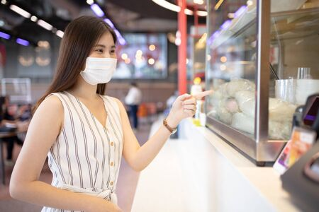 Asian woman sitting separated in restaurant eating food .keep social distance for protect infection from coronavirus covid-19, restaurant and social distancing concept. 免版税图像