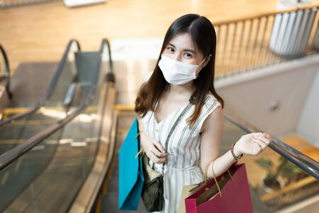 Asain woman in shopping. Happy woman with shopping bags enjoying in shopping.lifestyle concept.Smiling girl  holding colour paper bag.Friends walking in shopping mall.