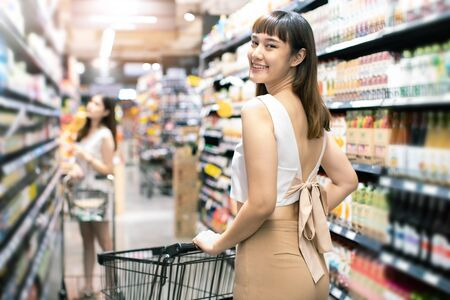 Asian woman wearing face mask push shopping cart in suppermarket . Girl choosing, looking somethings to buy at shelf during coronavirus crisis or covid19 .happy lifestyle or shopaholic concept.