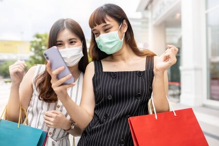 Asian woman wearing face mask. Happy woman with shopping bags enjoying in shopping. Girl holding colour paper bag.Friends walking in shopping mall.time shopping coronavirus crisis or covid19 outbreak