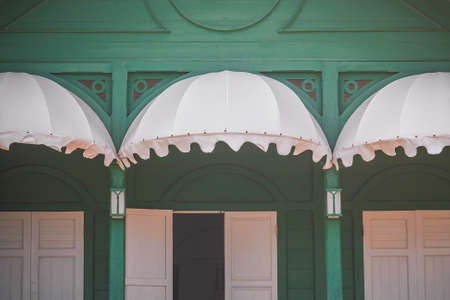an awning: White Awning And Window With Shutters Green Frame. Stock Photo