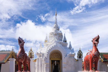 ancient lion: Lamphun, Thailand - December 10, 2014: Ancient Arched Entrance And The Pair Sculptured Of Lions Animals In Fiction Inside Wat Phra That Hariphunchai At Blue Sky Background.