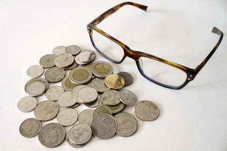 slump: Baht Thai Coins Stacked And Eyeglasses Isolated On White Background.