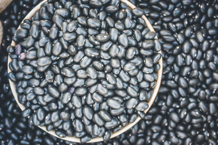 sprawled: Close-Up View Of Black Beans Scattered Beans Around On A Cup With Beans Background. (View From Above)
