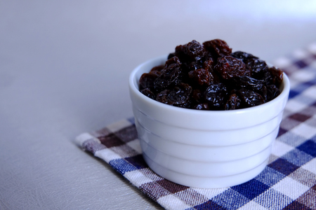 dried black raisins pile up in white cup 스톡 콘텐츠