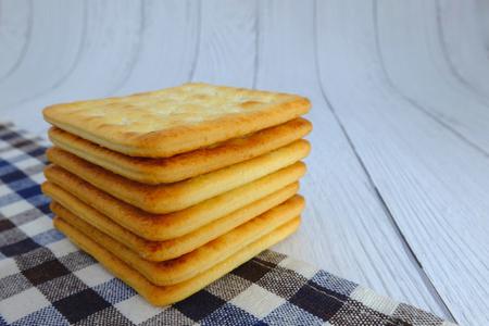 Cracker squares stacked, Cracker squares stacked on plaid fabric, Cracker squares stacked on white wood background Banque d'images - 122393823