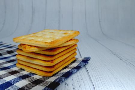 Cracker squares stacked, Cracker squares stacked on plaid fabric, Cracker squares stacked on white wood background Banque d'images - 122393899