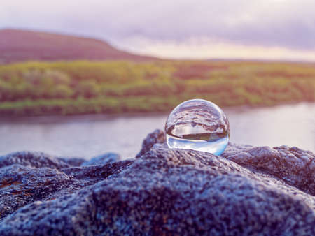 Magic glass ball on old stones. In the background is a river, a spring forest and a cloudy sky