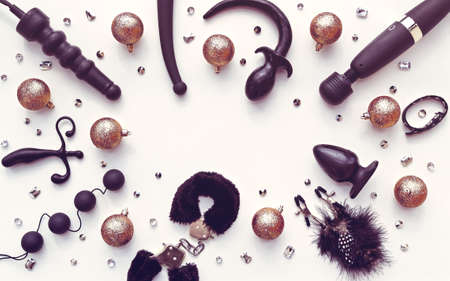 Various sex toys (dildo, anal balls, vibrator, fur handcuffs and others), golden christmas balls and krsitalles are arranged in a circle. New Year or Christmas background