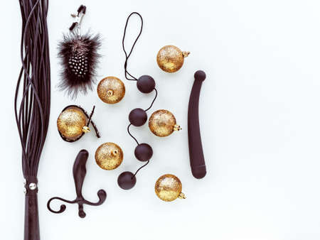 Various black sex toys and golden christmas balls are on a light background.