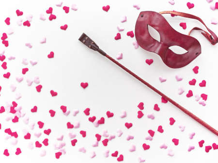 The Venetian mask and leather whip are on a light background with pink and red heart made of cloth. Romantic background for goods from a sex shop, costume party, Valentines Day