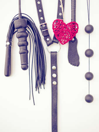 Various sex toys (dildo, whip, harness, anal balls and others) hang on a light background. Together with them hangs a red wicker heart. Image for advertising Valentine's Day 版權商用圖片