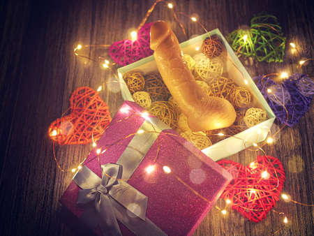 A flesh-colored dildo is in an open gift box. Around are wicker hearts of different colors and a luminous garland. Romantic background for Valentines day or love card Stock Photo