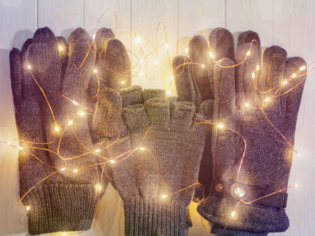 Three pairs of gloves made of wool are on a wooden background with a luminous garland. Image for advertising clothing store for the season of sales Stock Photo