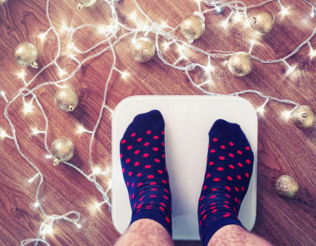 The man got up on white electronic scales after celebration of New Year and Christmas. His feet is dressed in blue socks with red dots. On a wooden floor, golden balls and a garland scattered