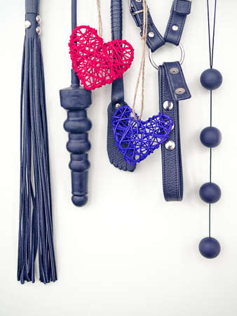 Various sex toys (dildo, whip, harness, anal balls) hang on a light background. 版權商用圖片