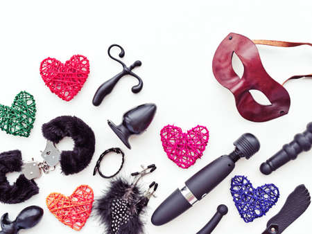 Black sex toys, brown leather venetian mask and colored figures of hearts from rattan are on a light background. Image for sex shop advertising (discounts, promo, banner, marketing) Stock Photo