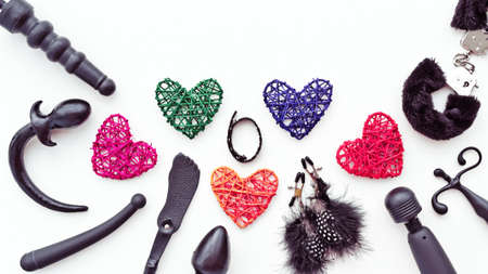 Sex toys and colored figures of hearts from rattan are on a light background. Image for sex shop advertising (discounts, promo, banner, marketing)