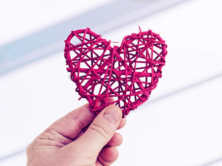 The man is holding a red wicker heart in his hand against the background of a light wall with diagonal stripes.