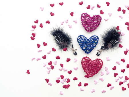 Three wicker hearts and nipple clamps with feathers (sex toy) are on a white background. Around these objects are scattered little figures of hearts. An image for Valentine's Day 스톡 콘텐츠