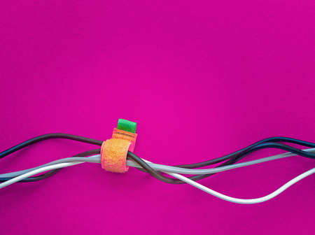 Wires for various purposes and colors are on a purple background. Fastening cables with Velcro tape. Repair cable works at home or in the office. Stock Photo
