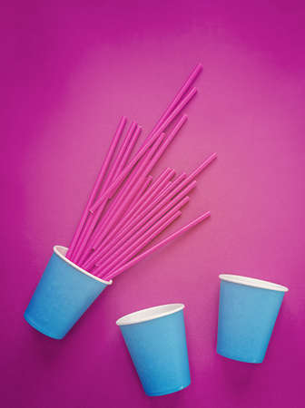 Three blue paper cups are on a purple background. From one of them there is a lot of straws for drinks. Background for a banner for a party, event. Artistic increase in the level of color and noise Banco de Imagens