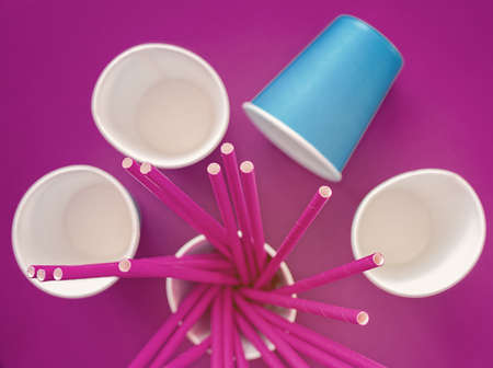 Empty paper cups are on a purple background. In one of the cups there are tubes for drinks. Waiting for a holiday, parties, celebrations, events. Artificial increase in color and noise Banco de Imagens