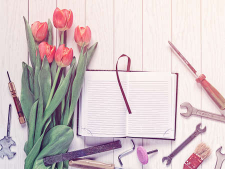An open diary or notebook with blank pages, a bouquet of red tulips and various tools are on a white wooden background. Image is suitable as a greeting on Labor Day or Father's Day Zdjęcie Seryjne