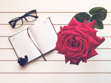 An open notepad with blank pages, black-rimmed spectacles, a cat figurine and a large red rose are on a white wooden background.