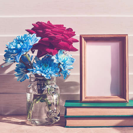 A red fresh rose along with blue chrysanthemums or chamomiles is in a glass jar. There is an empty wooden frame on the stack of books. White wooden background