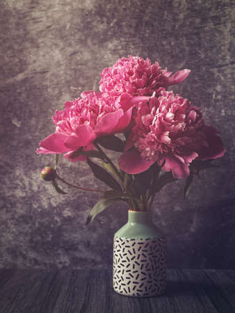 A bouquet of red and pink peonies in a vase with a pattern. Dark stone background.
