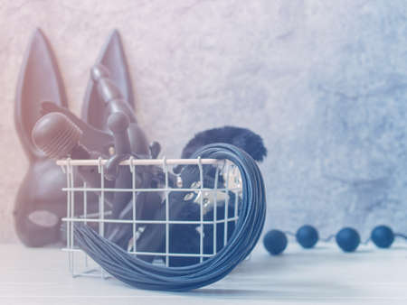 Various sex toys (vibrator, whip, dildo) are in a white metal basket. Behind is a black mask with rabbit ears and balls. Gray background with cracks and scuffs. Minimal composition.