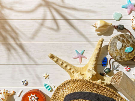 Vacation or trip planning concept. Layout with various marine items and travel souvenirs (starfish, straw hat, shells, miniature figures of boats, anchors). White wooden background. Copy space.