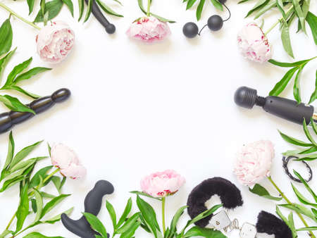 Flower layout for a shop. Various toys (didlo, handcuffs, balls and other) are on a white background. The background is decorated with pink peonies. Flat lay. Copy space