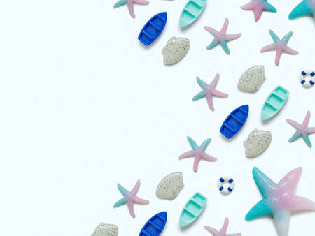 Creative travel background. Layout of various sea figures (starfish, boats, shells, lifebuoy). Preparing for vacation and travel. Flat lay. Copy space.