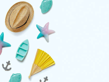 Creative travel background. Layout of various sea figures (starfish, boat, anchor, shells), a straw hat and a paper fan. Preparing for vacation and travel. Flat lay. Copy space. 免版税图像