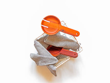 A wooden fork and a spoon for serving salad, together with a gray waffle towel, are in a wicker metal basket. White background. Kitchen concept. Top view.