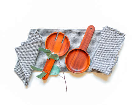 A wide wooden fork and a spoon for serving salad and a branch of eucalyptus are on a gray waffle towel on a white background. Kitchen concept. Top view. Flat lay. Stockfoto