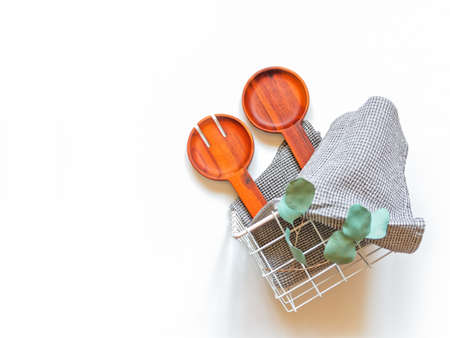 A wide wooden fork and a spoon for serving salad, a waffle gray towel and a branch of eucalyptus are in a wicker white metal basket. Kitchen concept. White background. Kitchen concept.