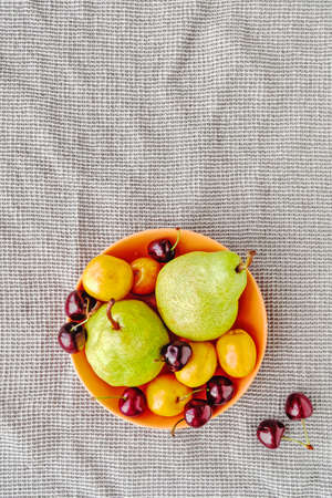 Fruit and berry composition. Green pears, ripe cherries and apricots are in an orange plate on a gray waffle towel. Summer layout about nutrition. Top view. Flat lay. Copy space.