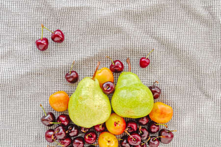 Fruit and berry composition. Green pears, ripe cherries and apricots are on a gray waffle towel. Summer layout about nutrition. Top view. Flat lay.