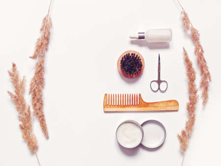 Accessories for the care of a beard and mustache are on a white background. Here are a wooden comb, a brush with stiff bristles, an open jar with balm or hair styling. Top view. lat lay.
