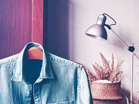The washed jeans shirt is on a wooden hanger. Behind is a cupboard, floor lamp and a bouquet of dried herbs in a wicker basket.